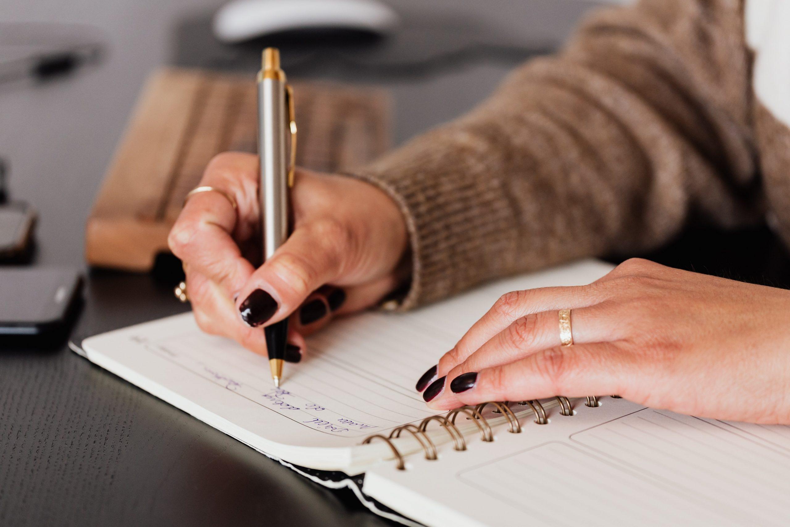 personne écrivant dans un cahier